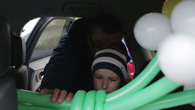Dad and son with bouquet of flowers sit in the car. Young man and a little boy going to meet mother. Roses and daisies. Raindrops hanging on the glass stock video footage