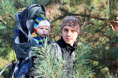 Dad and Son. Dad brings his son behind in a backpack Stock Photography