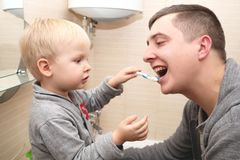 Dad and son brush their teeth in the bathroom. Father Brushing Teeth to Child stock image