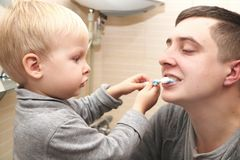 Dad and son brush their teeth in the bathroom. Father Brushing Teeth to Child stock photography