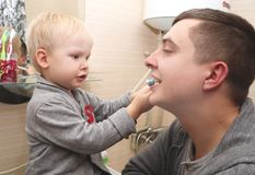Dad and son brush their teeth in the bathroom. Father Brushing Teeth to Child stock images