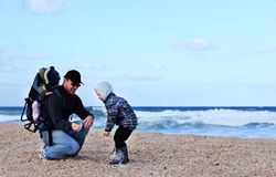 Dad and son collect shells Stock Photography