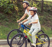 Dad and son cycling Royalty Free Stock Images