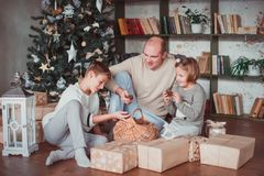 Dad, son and daughter sitting at the Christmas tree. Warm colour. They `re watching a basket of cones royalty free stock photo