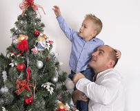 Dad with son decorate the Christmas tree. Little boy sitting on his father's hands and decorate the Christmas tree together Royalty Free Stock Images