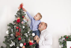 Dad with son decorate the Christmas tree. Little boy sitting on his father's hands and decorate the Christmas tree together Royalty Free Stock Photo