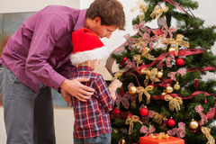 Dad with son decorating the tree Stock Image
