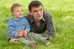 Dad and son discovering the world. Father and his son are lying on the green meadow Royalty Free Stock Photos
