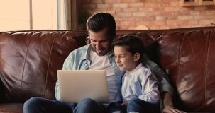 Dad and son discuss purchase buy on internet using laptop