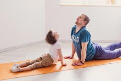 Dad son do sport at home. The father teaches child a healthy lifestyle. Parenthood