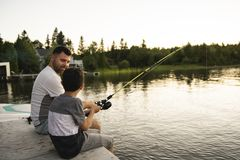 Cool Dad and son fishing on lake. A Dad and son fishing on lake stock photos