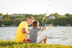 Dad and son fishing from shore Stock Image