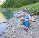 Dad and son are fishing together in a lake in the mountains Royalty Free Stock Photo