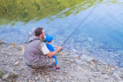 Dad and son are fishing together in a lake in the mountains Stock Photos