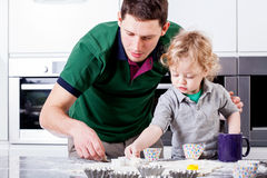 Dad and son focused on baking Stock Image