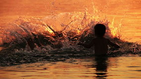 Dad with son fooling around in ocean sunset waves stock footage
