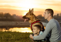 Dad and son and German shepherd in nature watching the sunset Royalty Free Stock Images