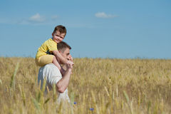 Dad and son going in the field Royalty Free Stock Photos