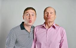 Dad and son on grey background Royalty Free Stock Photos