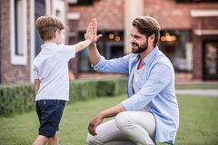 Dad and son. Handsome bearded dad is giving his cute little son a high five and smiling while they are playing together outside stock image