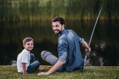 Dad with son. Handsome dad with his little cute sun are playing baseball on green grass lawn royalty free stock images