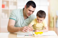 Dad and son have a fun painting with watercolor paints. Dad and kid son have a fun painting with watercolor paints Royalty Free Stock Photo