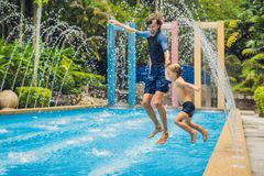 Dad and son have fun in the pool.  Stock Photo