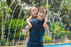 Dad and son have fun in the pool.  stock images