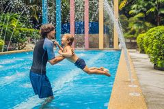 Dad and son have fun in the pool.  stock photography