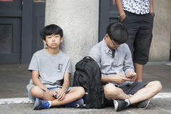 Dad and son have a rest, sitting on the sidewalk Royalty Free Stock Images