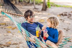 Dad and son having fun in a hammock with a drinks royalty free stock image