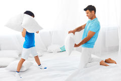 Dad and son having fun. Pillow fight. Dad and son having fun . Pillow fight in the bed at home. Happy parenthood stock images