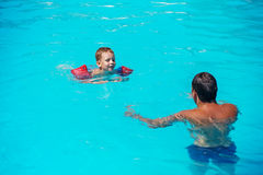 Dad and son having fun in swimmming pool Royalty Free Stock Images