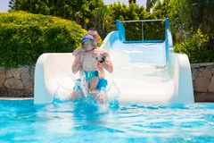 Dad and little son having fun on waterslide. Dad and son having fun on waterslide during sun holidays Royalty Free Stock Images
