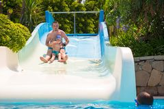 Dad and little son having fun on waterslide. Dad and son having fun on waterslide during sun holidays Stock Images