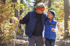 Dad and son hiking in forest embrace looking at each other Royalty Free Stock Photos
