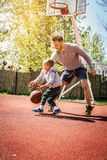 Dad and son. Dad and his son playing basketball royalty free stock photo
