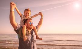 Dad with son on his shoulders looking at the horizon in the wate. A dad with son on his shoulders looking at the horizon in the water at the sea stock photo