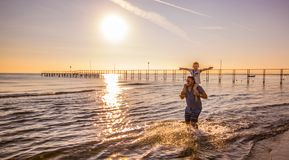 Dad with son on his shoulders walks in the water at the sea. A dad with son on his shoulders walks in the water at the sea royalty free stock photos