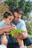 Dad and son inspecting leaf with a magnifying glass. In the park Stock Photos