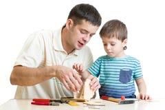 Dad and son kid make nesting box Royalty Free Stock Photos