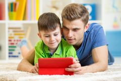 Dad and son kid play with tablet computer indoors Stock Photo