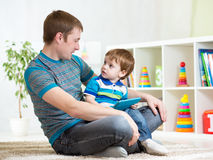 Dad and son kid play with tablet computer indoors Royalty Free Stock Image
