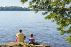 Dad and son lake fishing. Father and son lake fishing together. They're using telescopic fishing rods, fishing line, floats, and baited fishing hooks. Man has Stock Photos