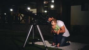 Dad and son looking through a telescope stock footage