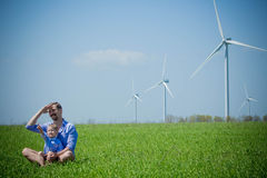Dad and son are looking at the wind generators royalty free stock photography