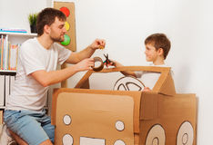 Dad and son making big toy cardboard car at home Royalty Free Stock Images