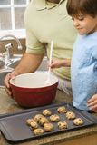 Dad and son making cookies. Royalty Free Stock Images