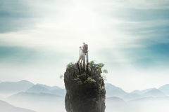 Dad and son on the mountain peak. Rear view of a young men standing on the mountain peak with his son and looking at the sky stock photography