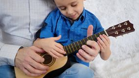 Dad and son play guitar together. Hands of dad and son close up. Music, lifestyle, parenting. Slow motion stock footage